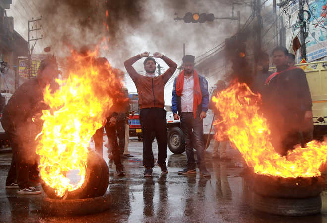 Demonstrators shout slogans next to burning tyres during a protest in Kishtwar town, in Jammu